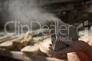 Female potter blowing dust from mud