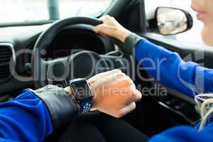 Cropped image of woman looking at smart watch during test drive
