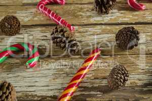 Candy canes and pine cones on wooden plank