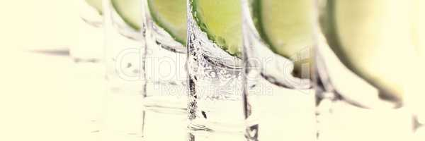 Alcoholic cocktail with lime and ice, isolated with reflection