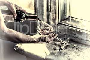 toned. Pouring wine on a old background