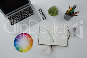 Laptop, spectacles, color swatch and stationery on white background