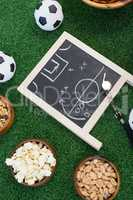 Strategy board, whistle and football on artificial grass