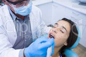 Dentist holding tools while treating woman at medical clinic