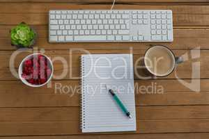 Coffee, keyboard, pot plant, notepad, pen and raspberry on wooden plank