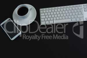 Keyboard, mobile phone and black coffee on black background