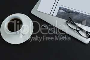 Black coffee, spectacles, pen, laptop and newspaper on black background
