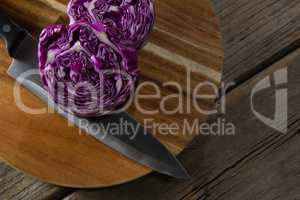 Red cabbage with knife on chopping board