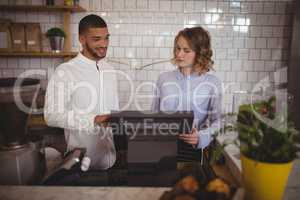 Male owner with waitress using computer at counter