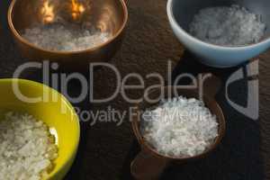 Salt in various bowl on black background