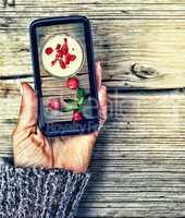 Healthy Eating. Smartphone in a female hand. display image of strawberry milkshake