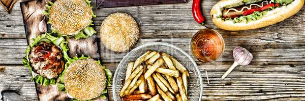 hot dogs and beer on a wooden table. Rustic style, top view homemade burgers with beef
