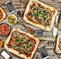 Friendly feast at home. Appetizing homemade pizza on a wooden table.