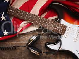 Old used guitar with headphones and American flag