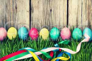 HAPPY EASTER Easter eggs in a green grass on a wooden background, authentic Easter decorations.