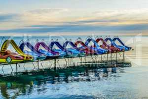 Colorful paddle bikes on calm summer lake.