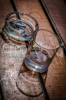 Empty whiskey glass and ashtray with cigarette sticks on wooden table.