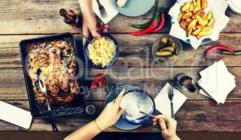 Couple of young people at the dinner table with a variety of foods, baked chicken legs, potatoes barbecue, beer, pickles and snacks,