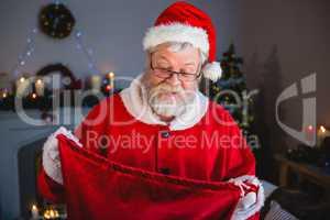 Surprise santa claus opening gift sack in living room