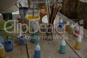 Watercolor cans and paintbrush in pottery workshop