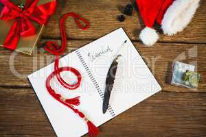 Wrapped gift, santa hat, diary and quill pen on wooden table in living room