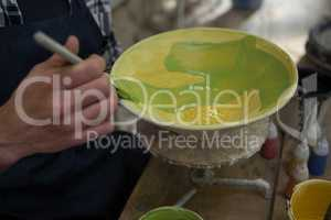 Male potters hand painting a bowl in pottery workshop
