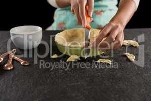 Woman slicing off extra dough from the mold