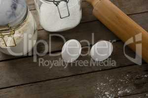 Rolling pin, eggs and glass containers on a wooden table