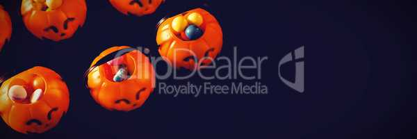 Jack o lantern containers with sweet food over black background