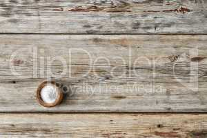 free space for text. Kitchen salt in a salt shaker on a wooden table,