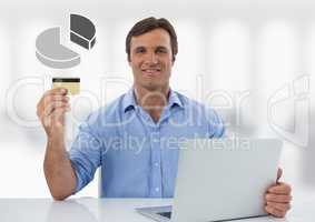 Businessman with laptop at desk with diagram pie chart and bank card
