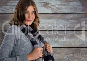 Woman against wood with warm scarf and jumper