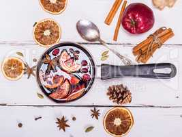 mulled wine with spices and fruits in an aluminum container