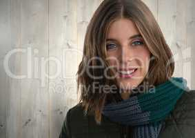 Woman against wood with warm scarf and coat