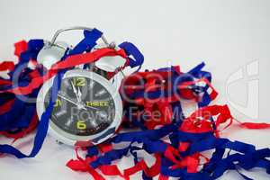 Alarm clock and streamers against white background
