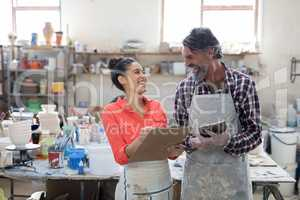 Male and female potter interacting in workshop
