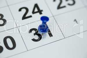 Blue pin push on day 31st of month end on white calendar