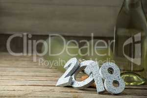 New year number 2018 and champagne bottles arranged on wooden surface