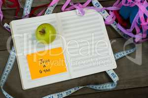 Diary with new year resolution join a gym and measuring tape