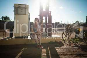 Woman sitting at petrol pump station