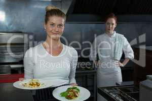 Female chefs holding food plates