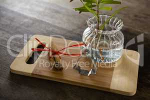 Wrapped cinnamons, cookie cutter and pot plant on chopping board