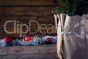 Christmas tree with decorations against wooden background