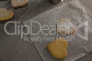 Raw heart shape cookies with sugar icing on wax paper