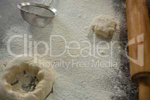 Dough, flour and stainer on table