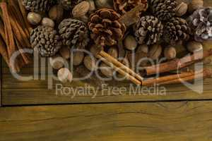 High angle view of walnuts with pine cones and cinnamon stick