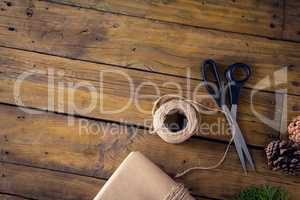 Fir, pine cone and wrapping materials on wooden table