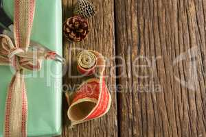 Scissors, pine cones and ribbon with wrapped gift box on wooden table
