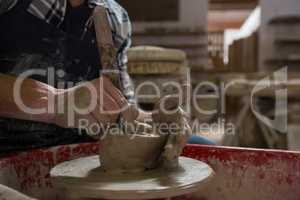 Male potter making a pot in pottery workshop