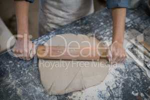 Female potter flattening the clay with rolling pin